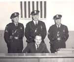A black and white photo of 3 uniformed police officers and a man in a suit