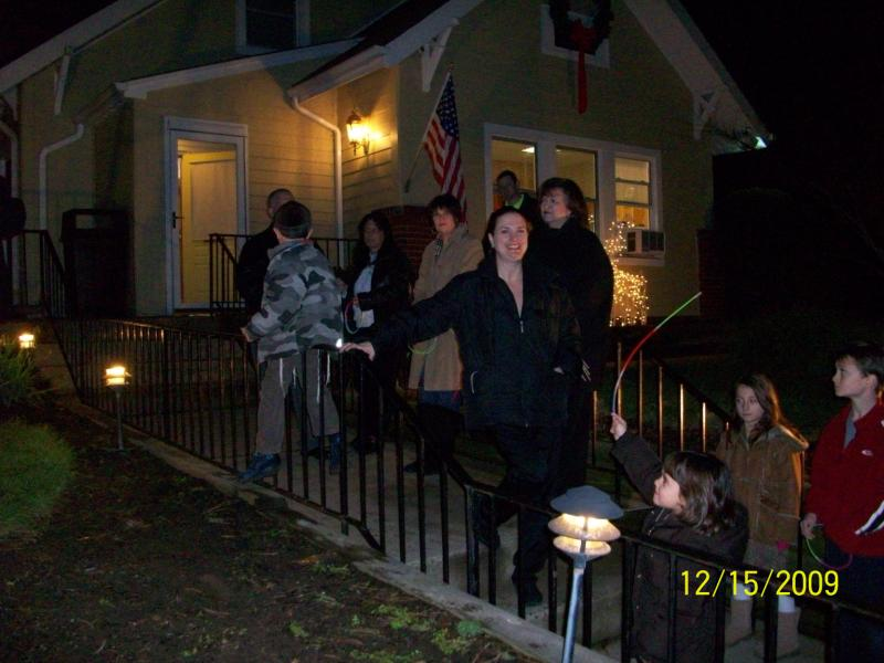 A crowd of people outsdie of a yellow house