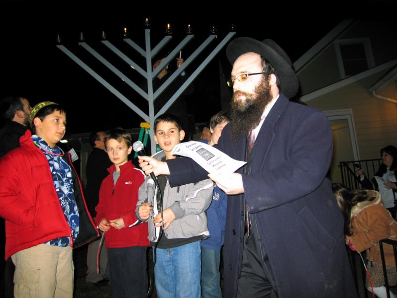 A man handing a microphone to a young boy