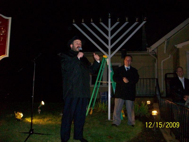 A man in front of a large menorah
