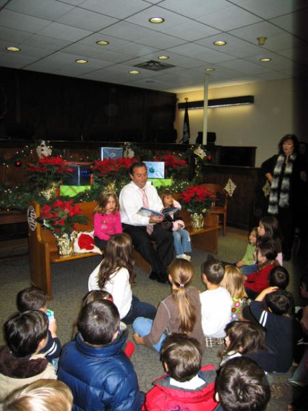 A man reading to a group of children at Christmas time