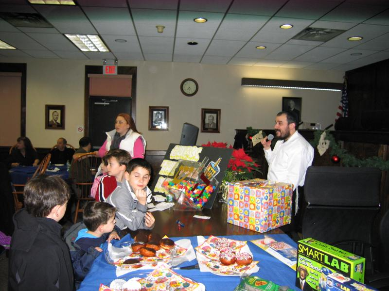Kids at a table of donuts and gifts