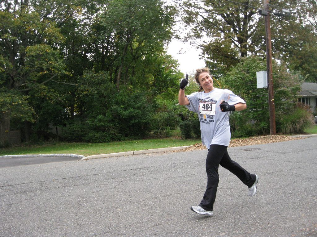 A woman running and giving a thumbs up