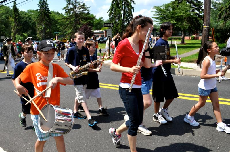 A parade of yound kids playing instruments