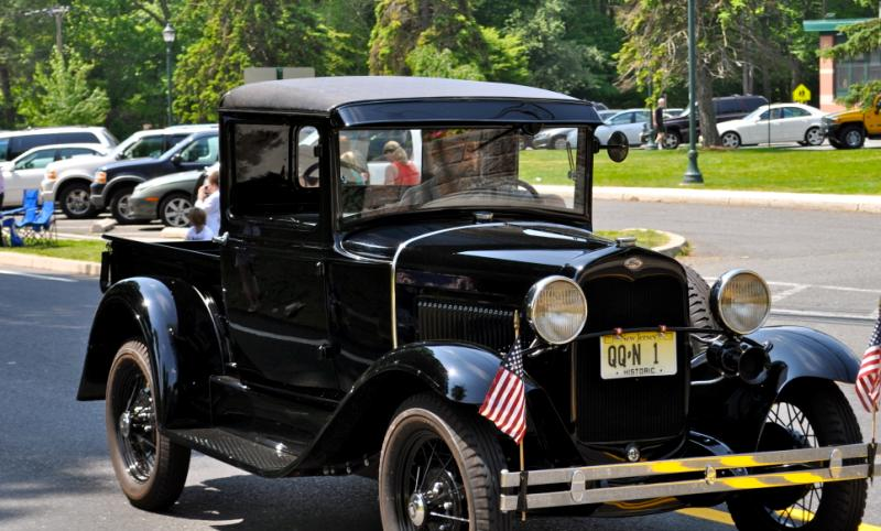 An old black car in a parade