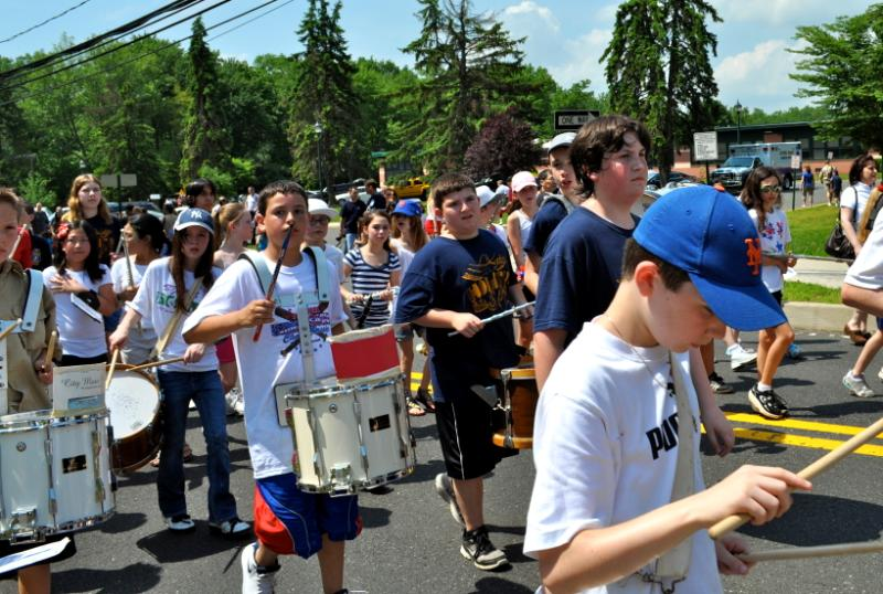 Kids in a parade playing drums