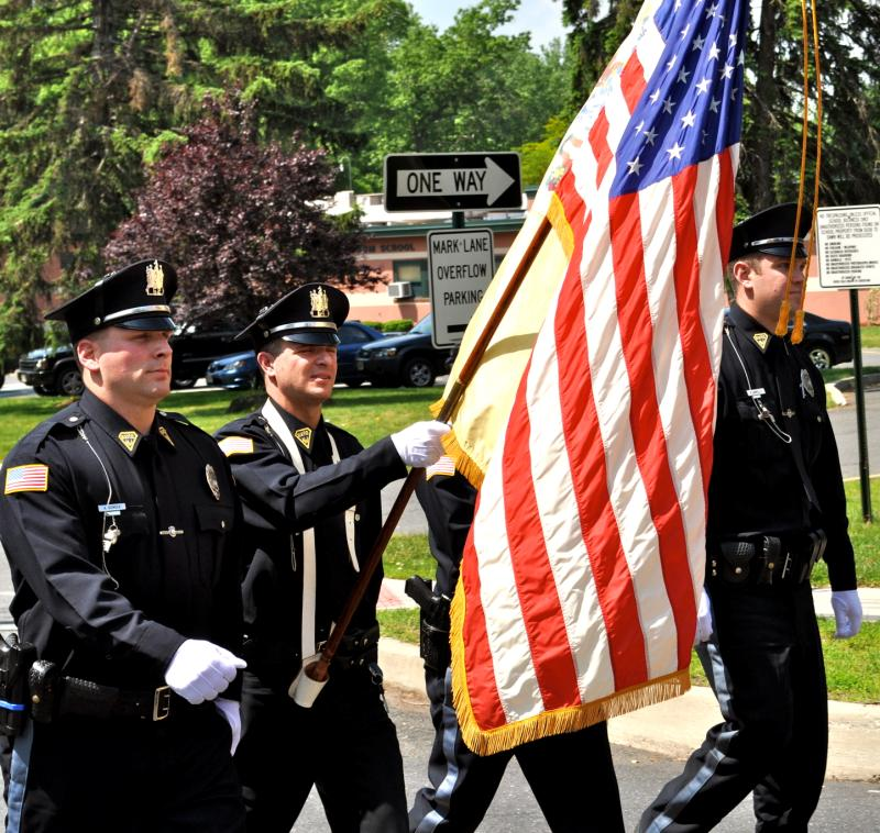 Uniformed officers in a parade with an American flag