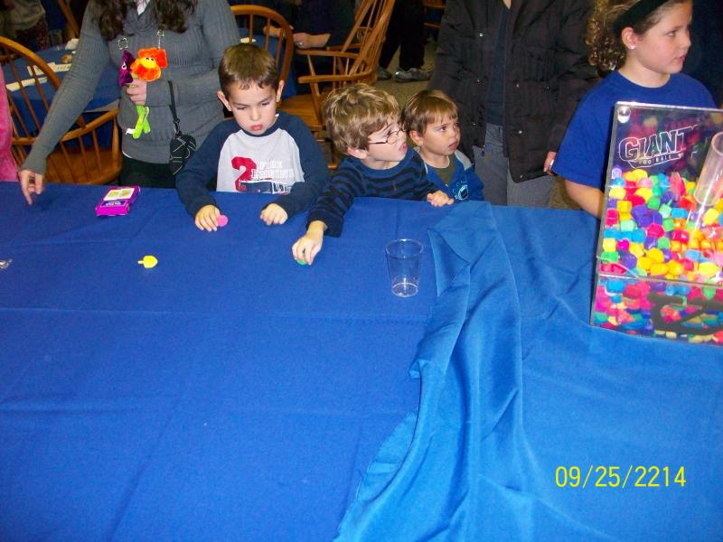 Kids standing at a blue table