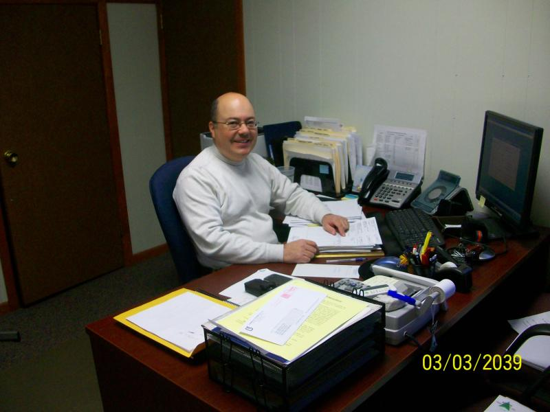 A man at a desk smiling